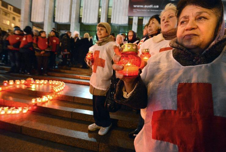 Ativistas de organizações públicas e pessoas infectadas pelo HIV segurar velas como eles comício em frente de uma fita vermelha definir com velas no centro da capital ucraniana de Kiev, em 29 de novembro de 2012. Getty Images
